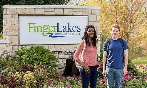 Students walking at the main entrance to Finger Lakes Community College.